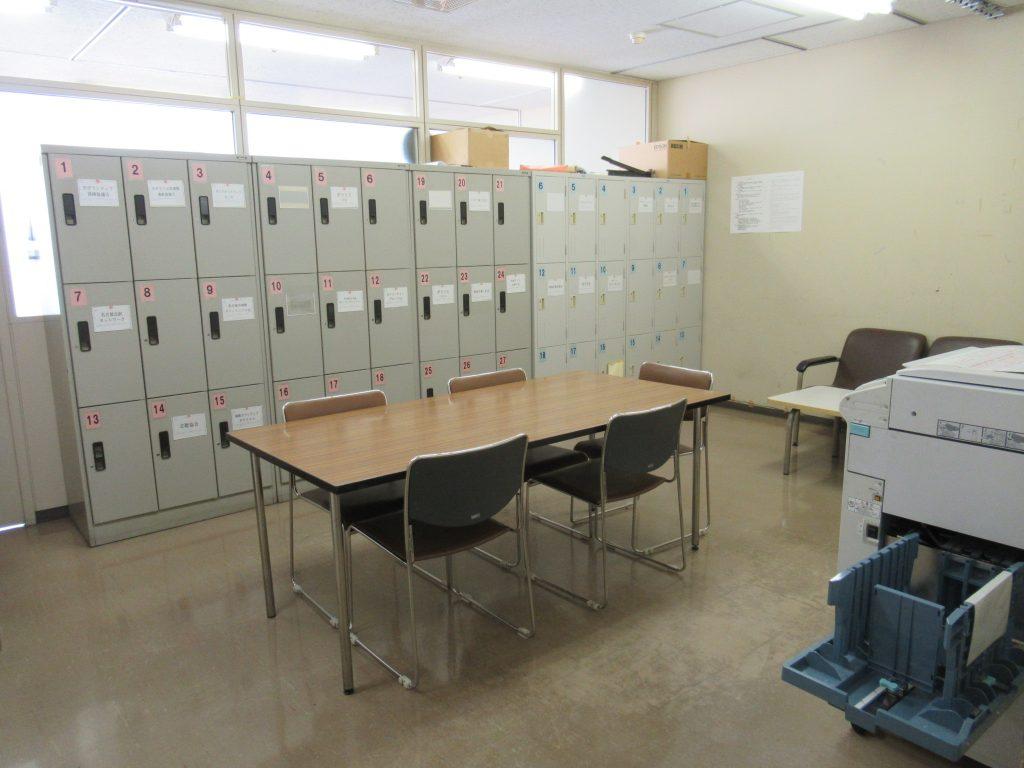 入口入ってすぐ右側にコピー機、部屋の中央に長机1本とイス4脚、部屋の奥壁付けで貸出用ロッカーがあります