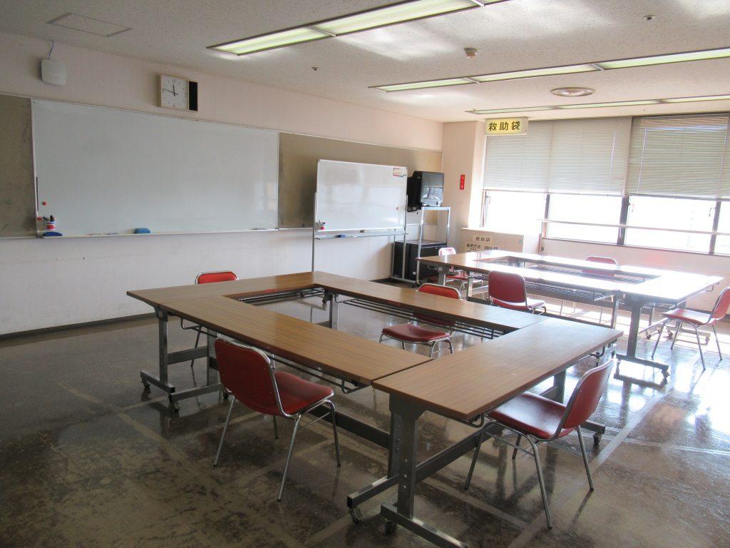 部屋の中央に「ロ」の字型に長机計4本が配置されている島が2つ。各机にはイスが1脚ずつ。 室内には壁面備え付けのホワイトボード1枚と可動式ホワイトボードが2台、VHSビデオ付テレビモニターが1台あります。