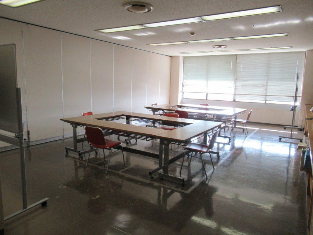 部屋の中央に「ロ」の字型に長机計4本が配置されている島が2つ。各机にはイスが1脚ずつ。 室内には可動式ホワイトボードが2台あります。