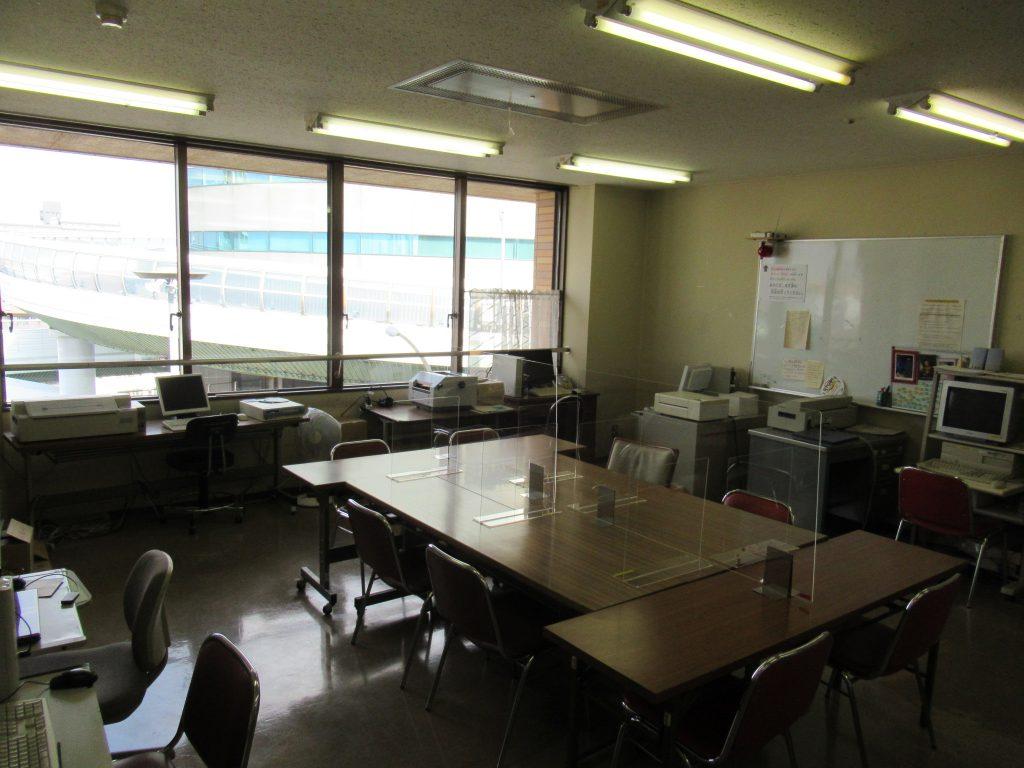 部屋の中央に長机4本を組み合わせた島があり、その周りにイスが計8脚あります。 部屋の各壁付けには、机があり、点訳ソフトを組み込んだパソコンや点字プリンタなどが置いてあります。