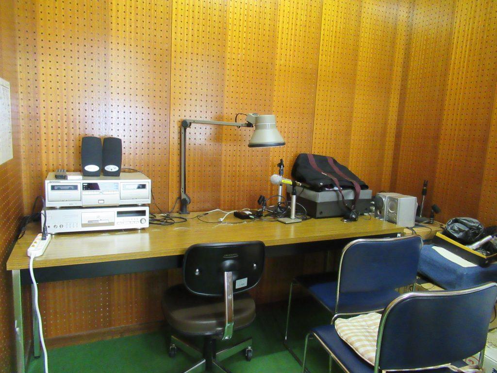 入口入った室内にある2つある録音編集スペースの中。 奥の壁付けで長机があり、机の上に各種機材があります。