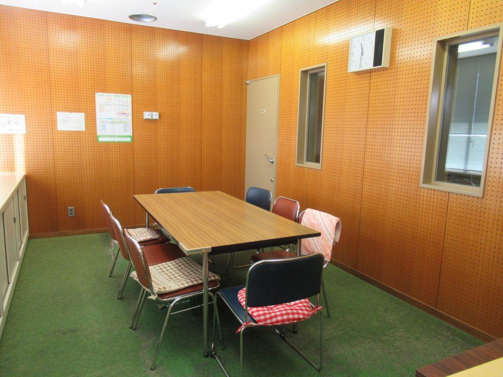 部屋に入ってすぐのところ。 部屋の中央に長机1本、その周りにイスが8脚あります。